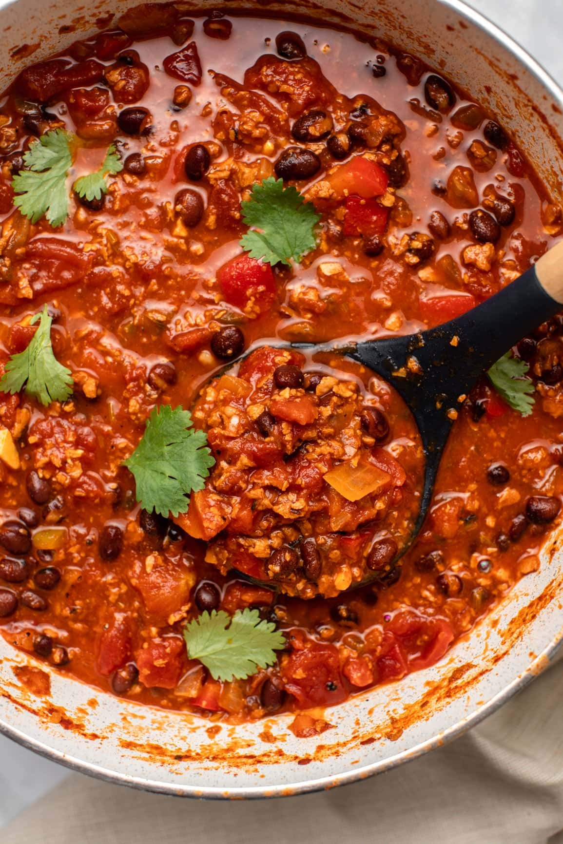 up close photo of cooked chili topped with fresh cilantro in pot with serving spoon