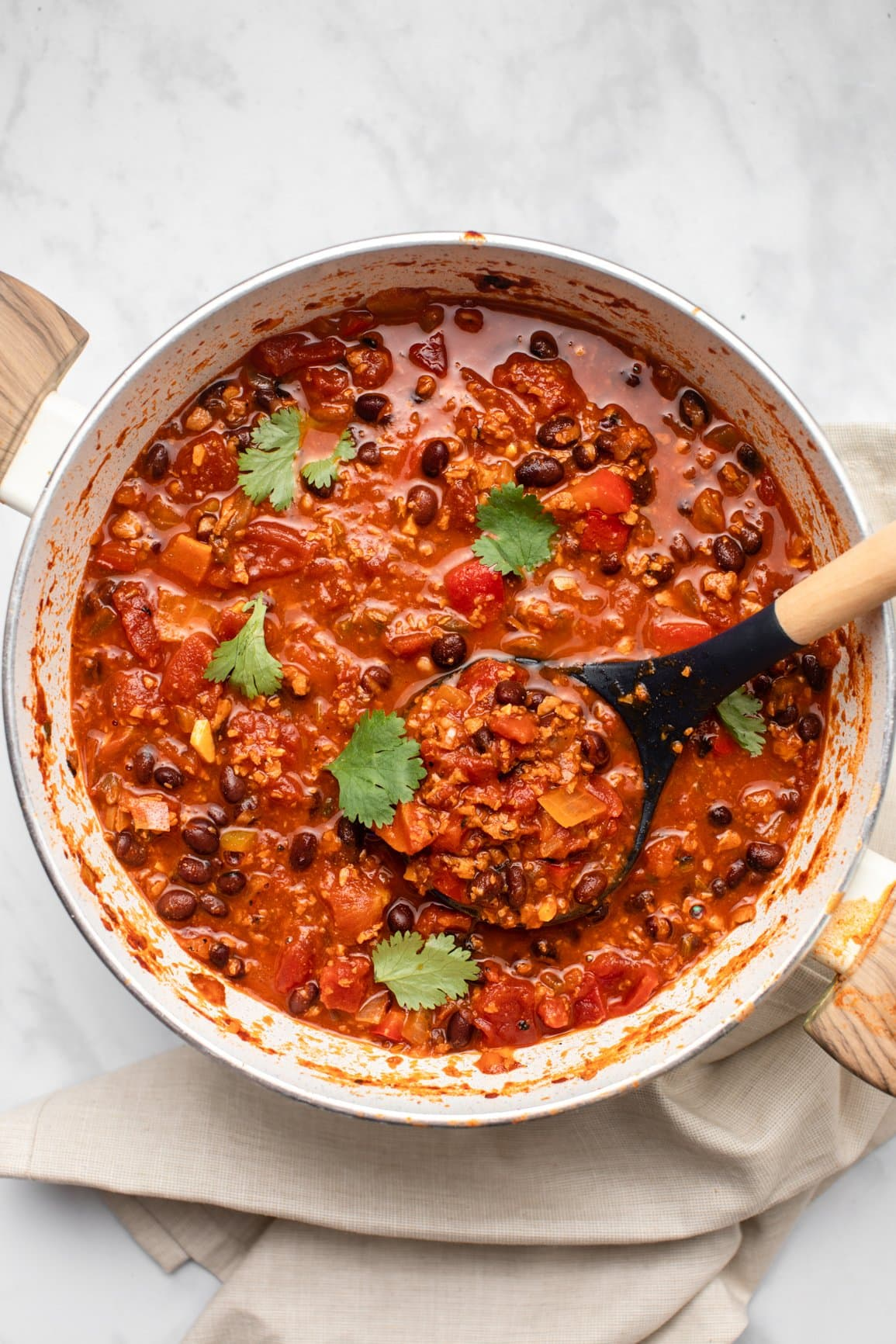 big pot of chorizo chili garnished with cilantro and with serving spoon