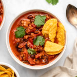 two bowls of vegan chorizo chili topped with cilantro and served with tortilla chips on the side