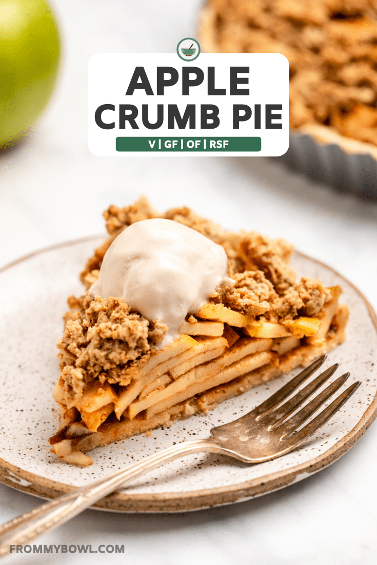 side shot of slice of apple crumb pie topped with vanilla ice cream