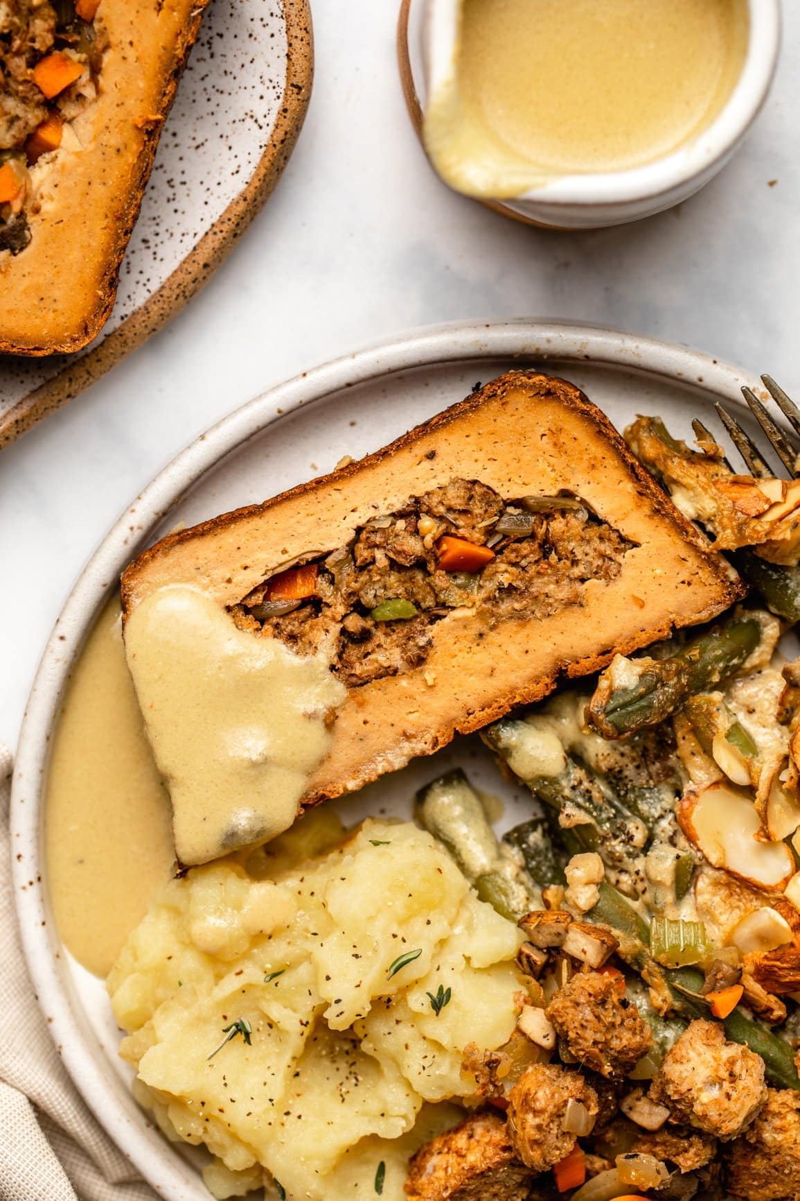 photo of slice of holiday roast on plate with mashed potatoes, gravy, green bean casserole, and stuffing
