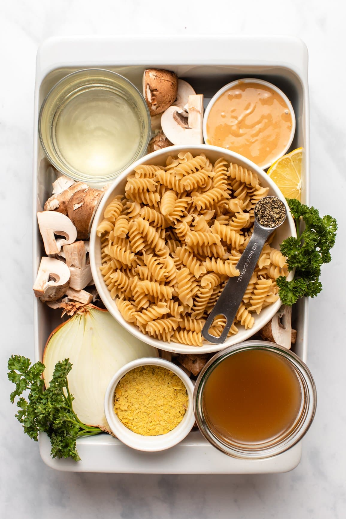 ingredients for vegan mushroom stroganoff in small containers organized inside of casserole dish