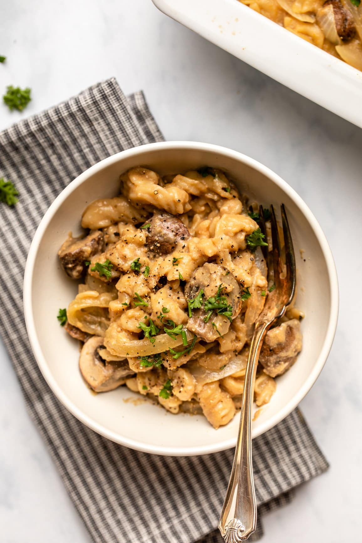 no boil vegan mushroom stroganoff in topped with parsley and black pepper in white bowl on marble countertop