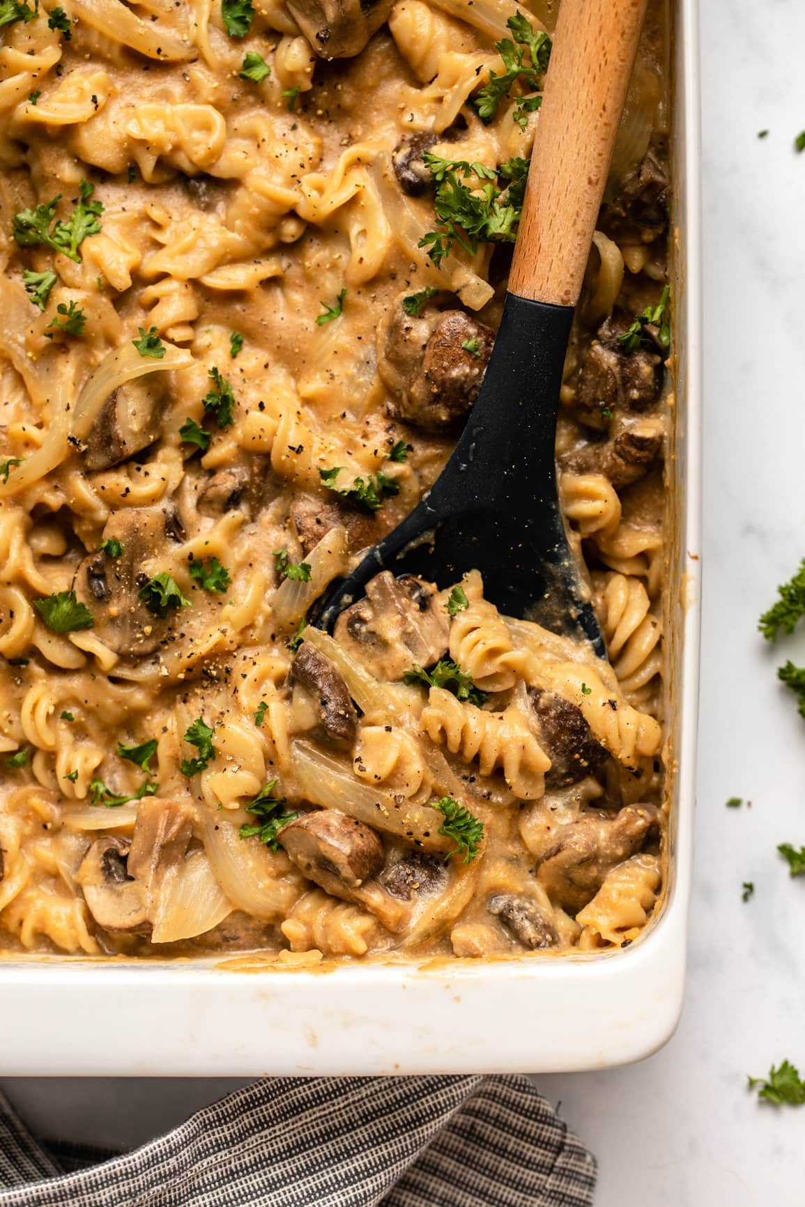 no boil baked vegan mushroom casserole topped with fresh parsley and wooden serving spoon