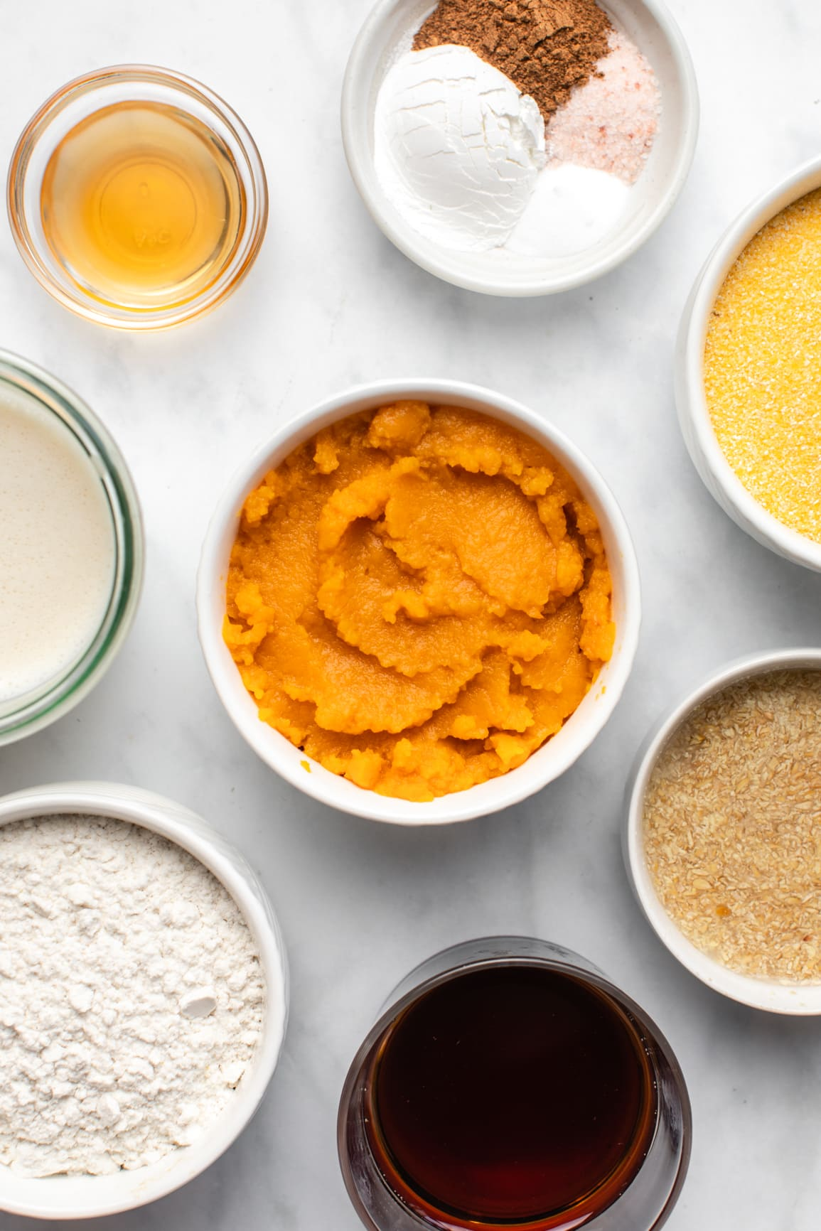 ingredients for pumpkin muffins in small white bowls on marble background