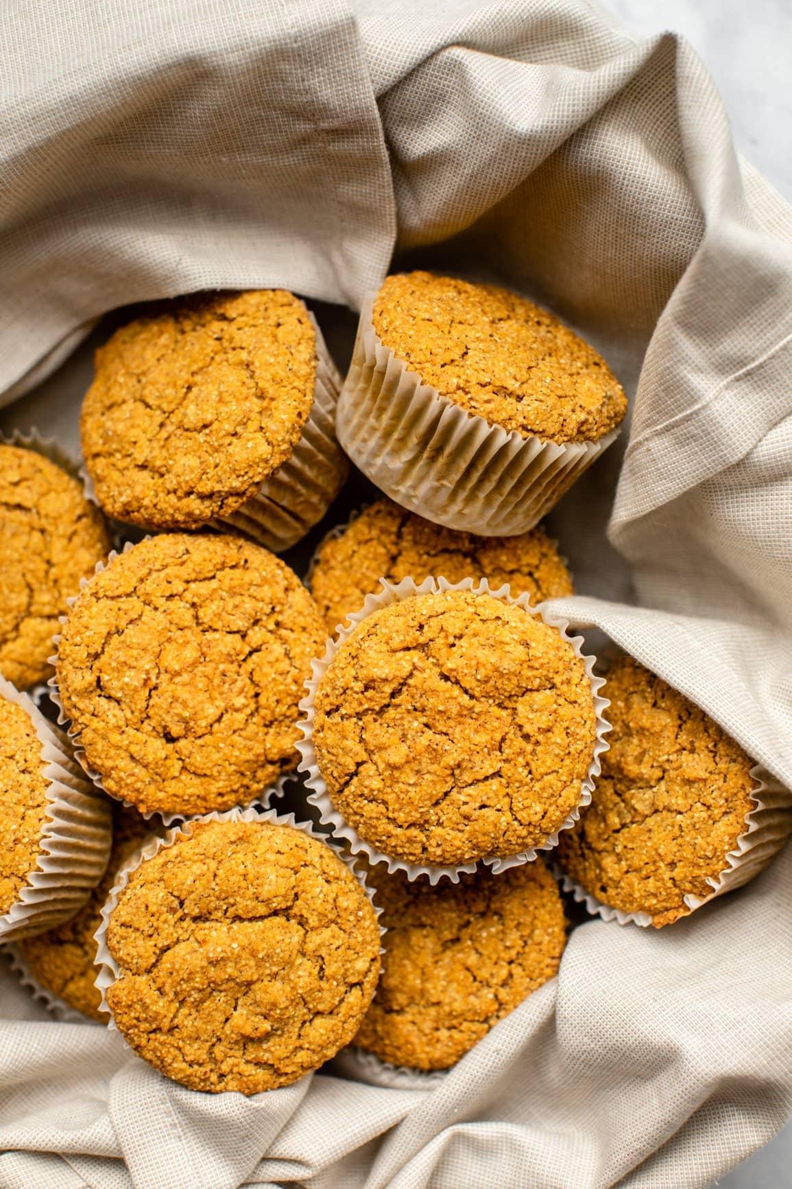 napkin-lined basket full of pumpkin muffins