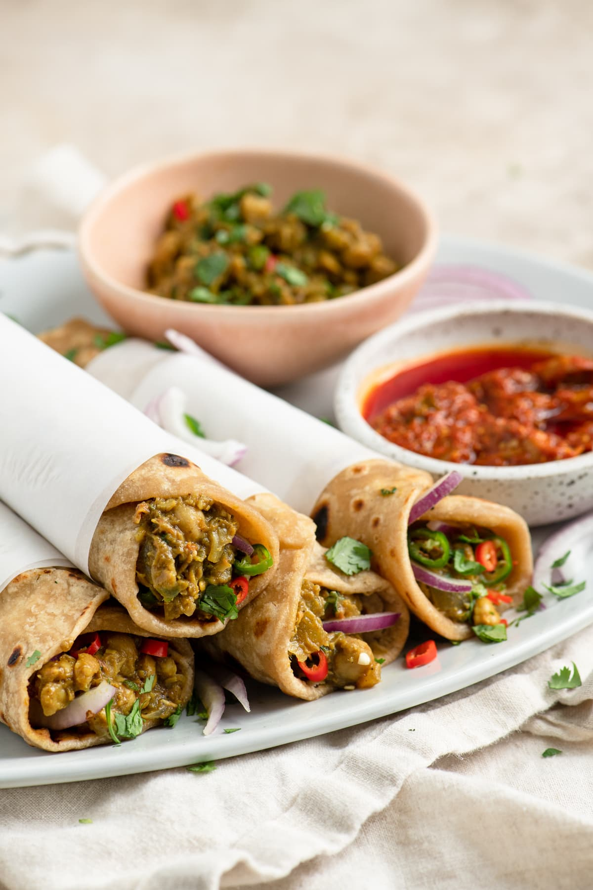 chana kathi tolls on serving plate next to mint chutney and aachar, or indian pickles