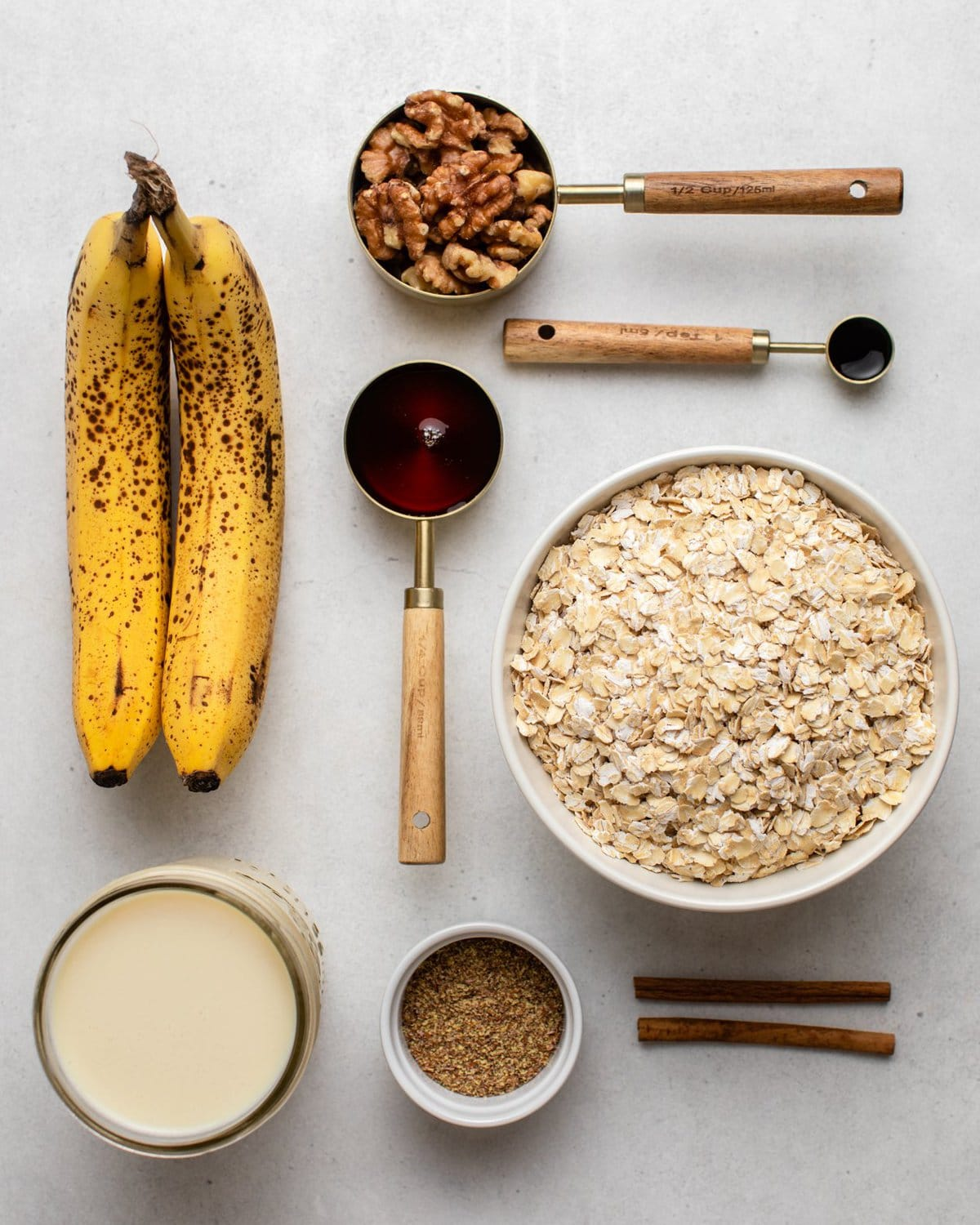 ingredients for banana bread baked oatmeal in measuring cups on white background