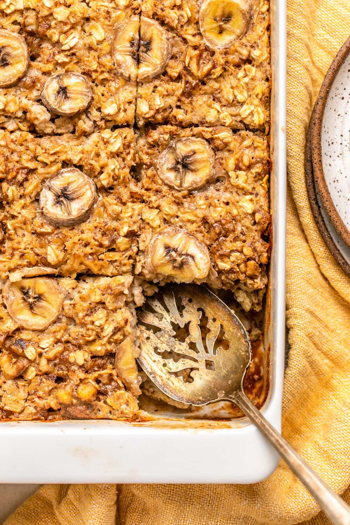 sliced banana bread oatmeal in white baking tray with yellow table linen
