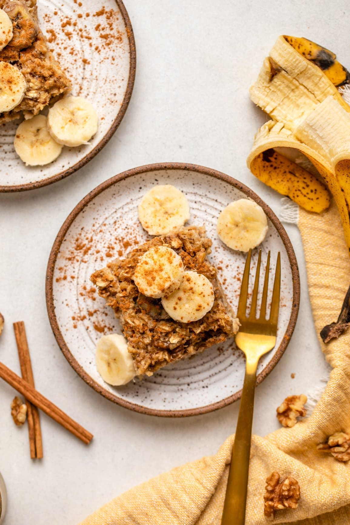 slice of baked banana bread oatmeal on small white plate topped with sliced banana and cinnamon