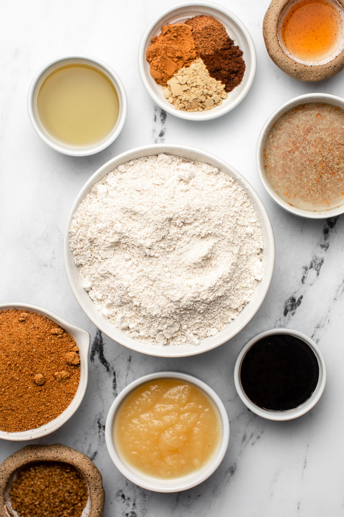 ingredients for gingerbread loaf in small white bowls on marble countertop