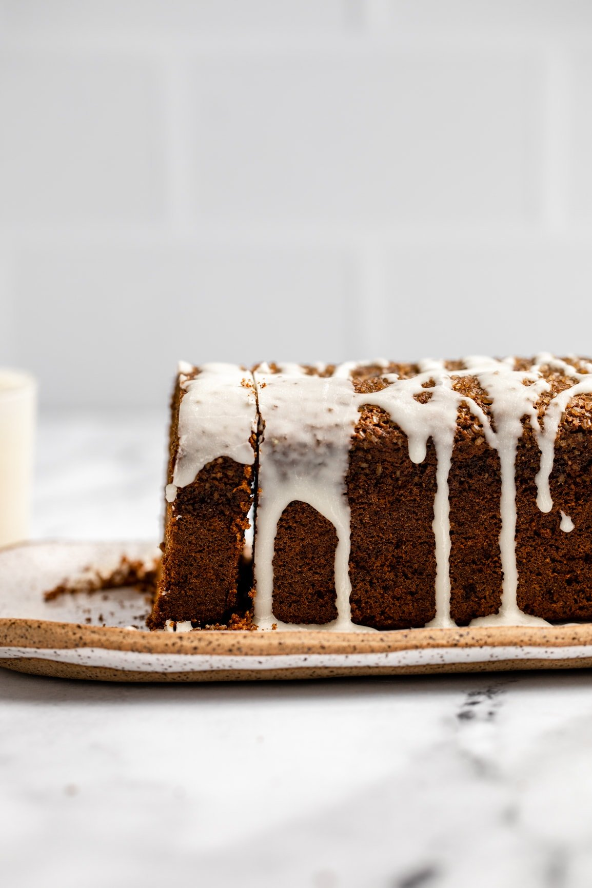 side shot of sliced gingerbread loaf with icing drizzled over the top of it