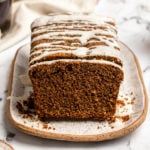 gingerbread loaf topped with icing sugar slices on a white serving tray next to cups of coffee