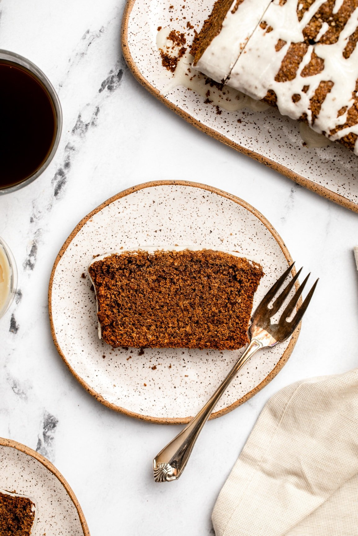 slice of gingerbread loaf on small white plate next to cup of coffee and rest of gingerbread loaf on white serving tray