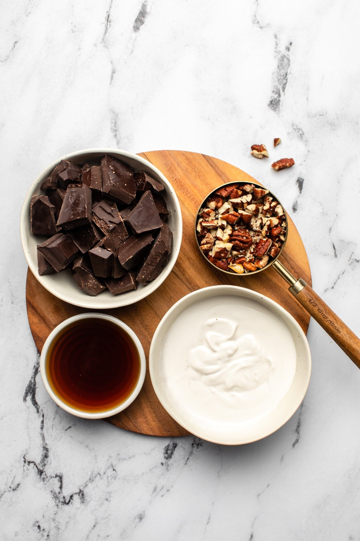 white bowls of coconut cream, chocolate, maple syrup, and pecans on wood cutting board