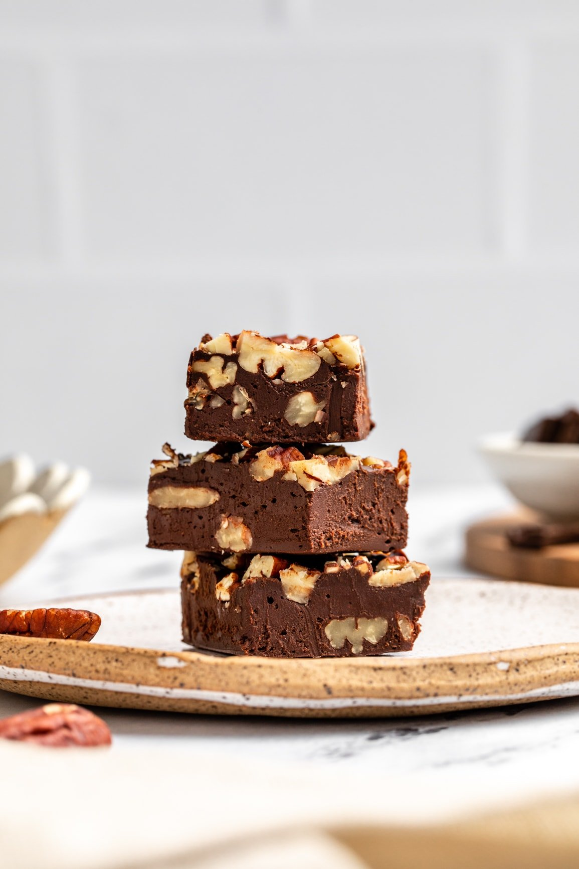 stack of maple pecan fudge on white speckled plate on marble countertop