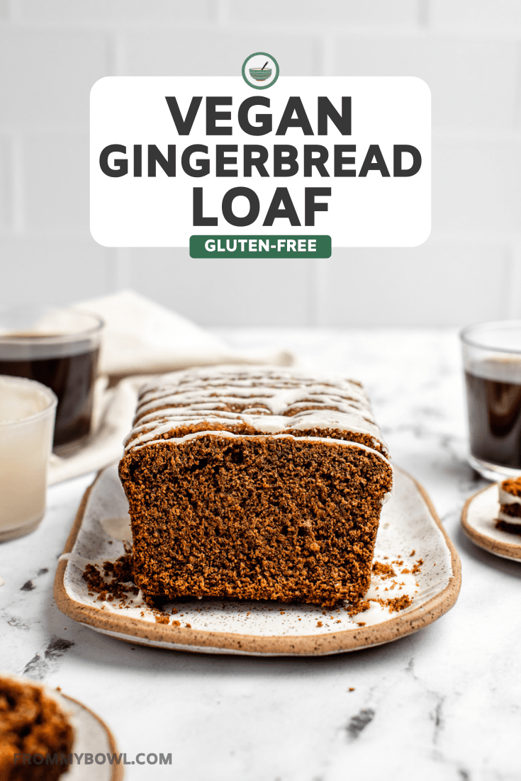 sliced gingerbread loaf topped with icing sugar on white serving tray next to cups of coffee on marble counter