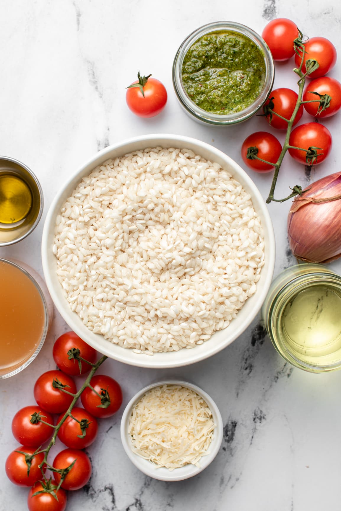 ingredients for risotto in small white bowls on marble countertop