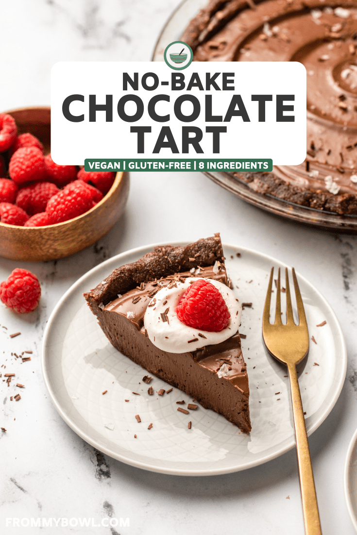 slice of no-bake chocolate tart topped with whipped cream and a raspberry on small white plate with gold fork