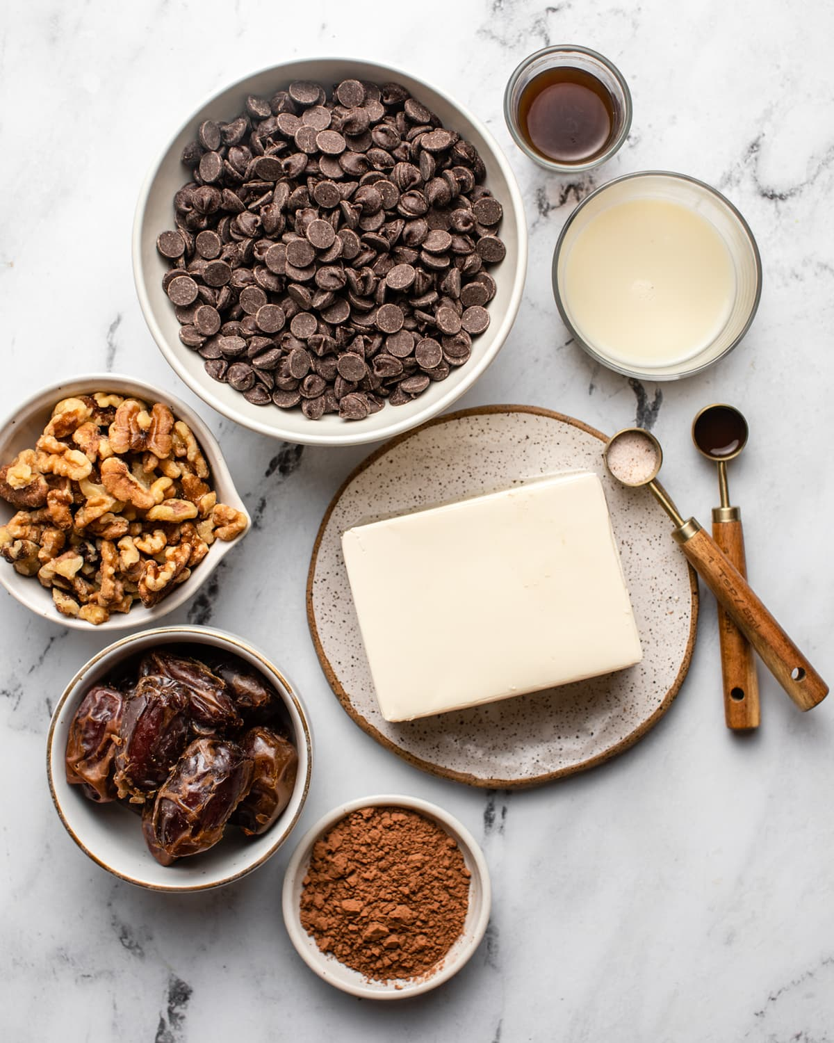 small bowls of chocolate chips, walnuts, dates, cacao powder, tofu, milk, coffee, vanilla, and salt on marble background