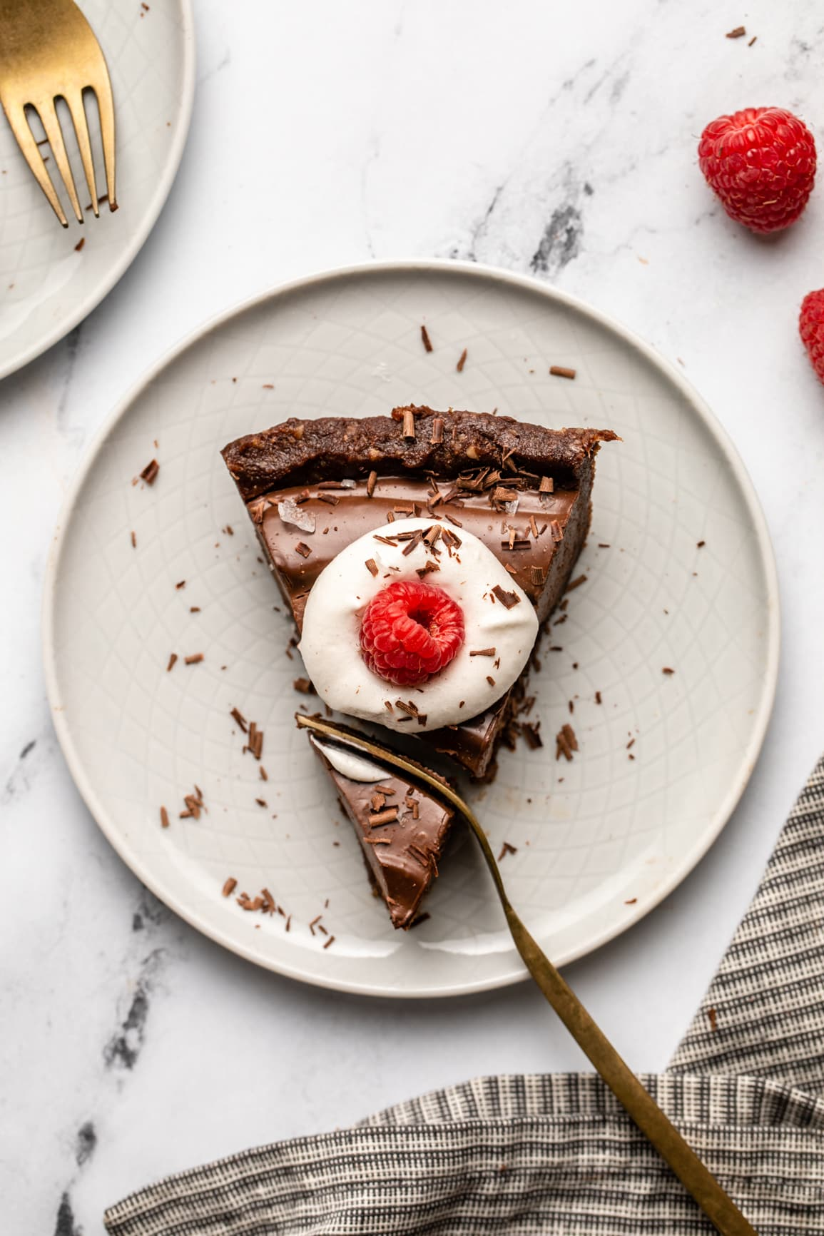 fork cutting into piece of no bake chocolate tart topped with coconut cream and a raspberry