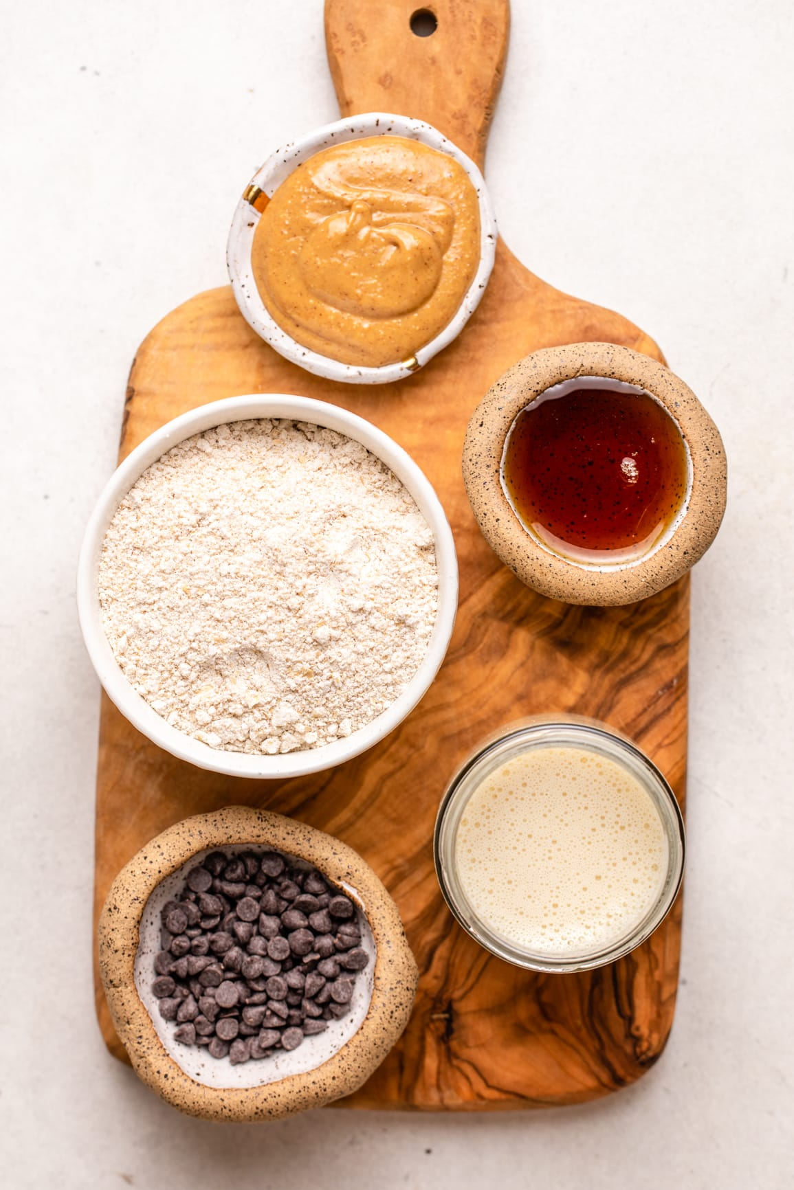 ingredients for pancakes in small containers arranged on wood cutting board