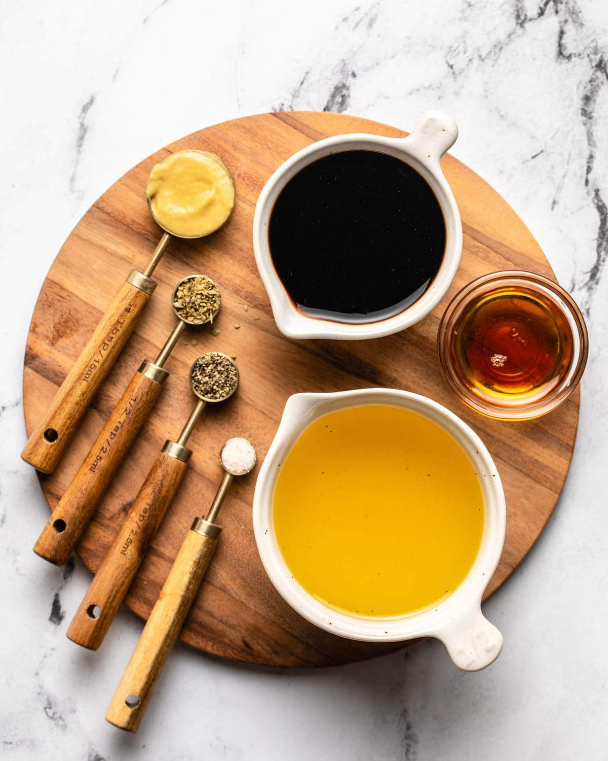 ingredients for balsamic vinaigrette in measuring cups on wooden serving board
