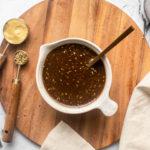 balsamic vinaigrette in white serving bowl on wood cutting board