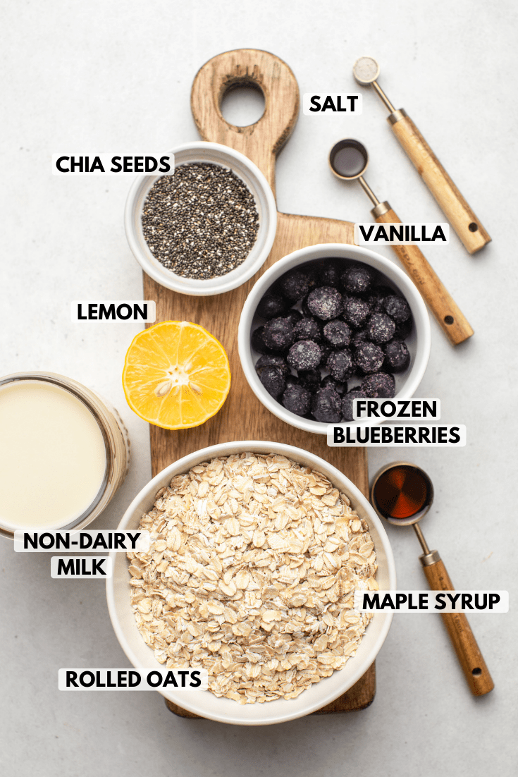ingredients for blueberry overnight oatmeal arranged on wood cutting board. Text labels read chia seeds, salt, vanilla, lemon, frozen blueberries, maple syrup, rolled oats, and non-dairy milk.