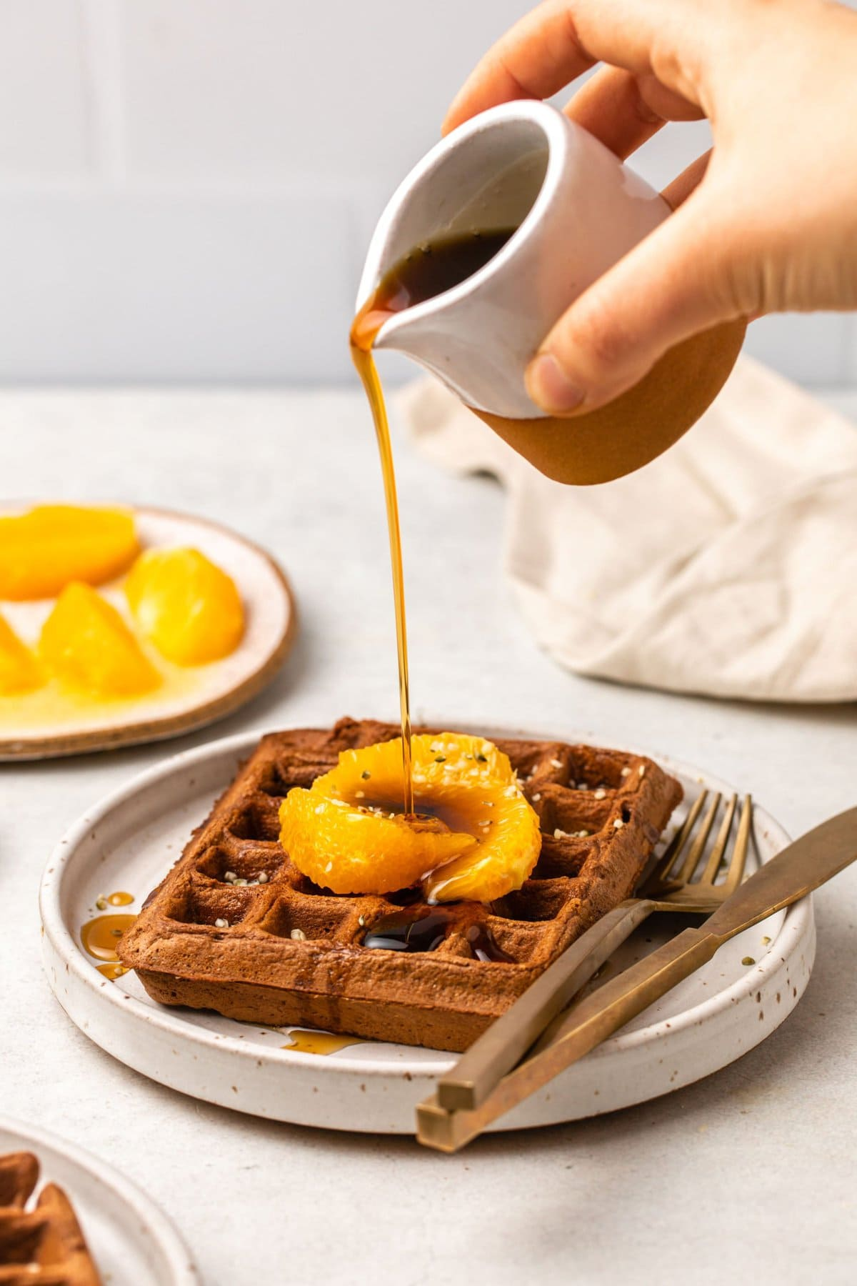 hand pouring ceramic container of maple syrup over a waffle topped with orange slices and hemp hearts