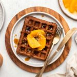 two chocolate orange waffles on small plates topped with sliced oranges, hemp hearts, and maple syrup