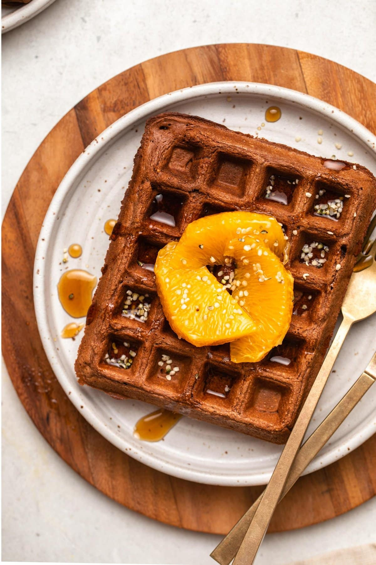 close-up photo of one chocolate orange waffle on white plate topped with hemp hearts orange slices and maple syrup
