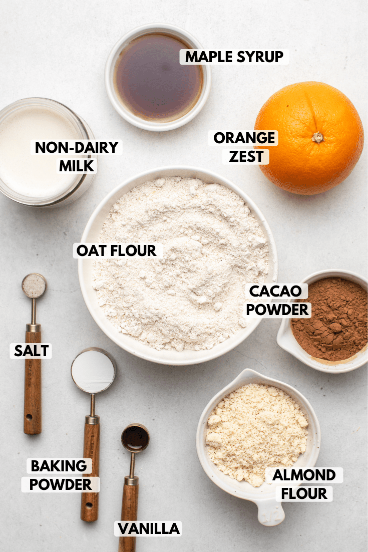 Ingredients for chocolate orange waffles in small white bowls on stone background. Text labels read maple syrup, non-dairy milk, orange zest, oat flour, cocoa powder, salt, baking powder, vanilla, and almond flour