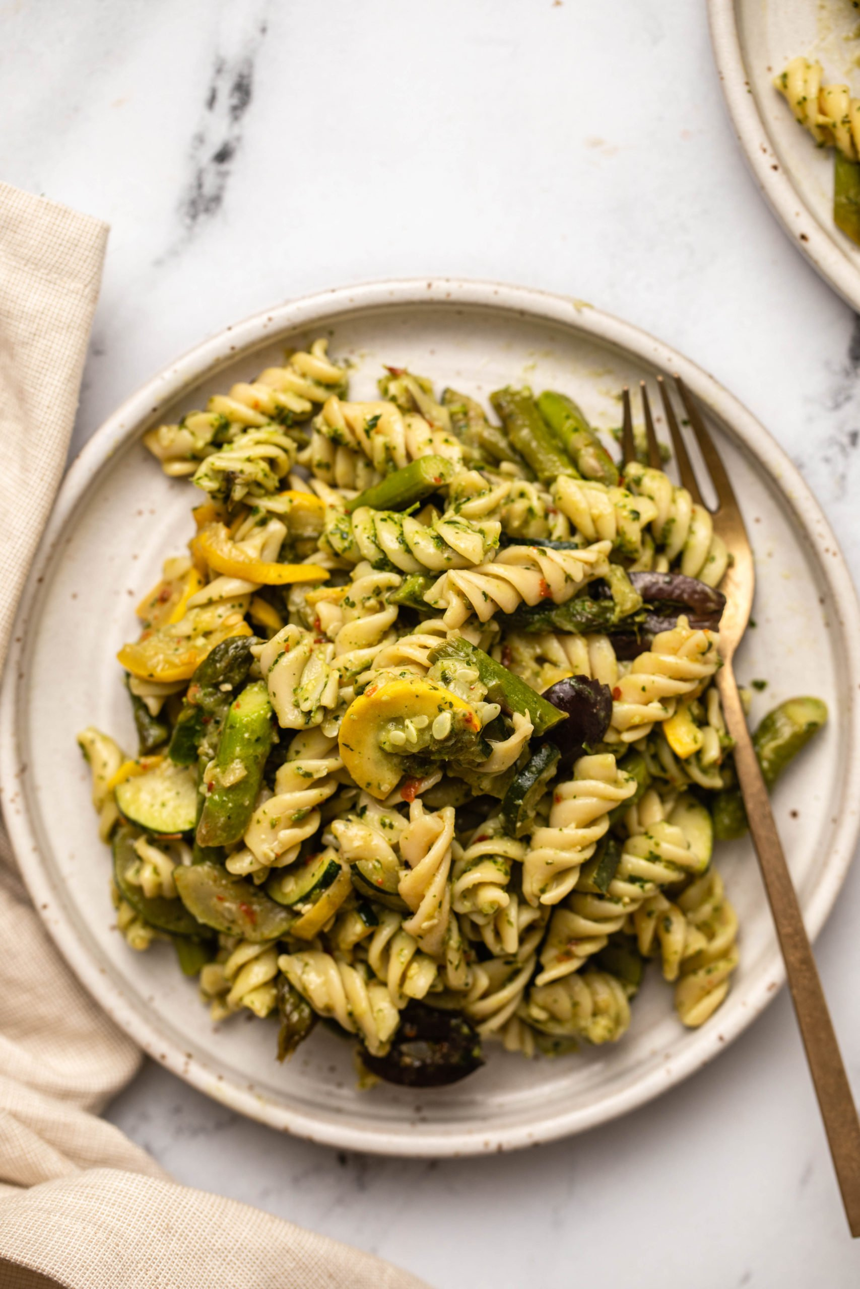 roasted spring vegetable peso pasta on white plate with gold fork