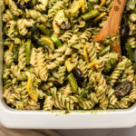 roasted spring vegetable and pesto pasta in white casserole dish with wooden spoon scooping into dish