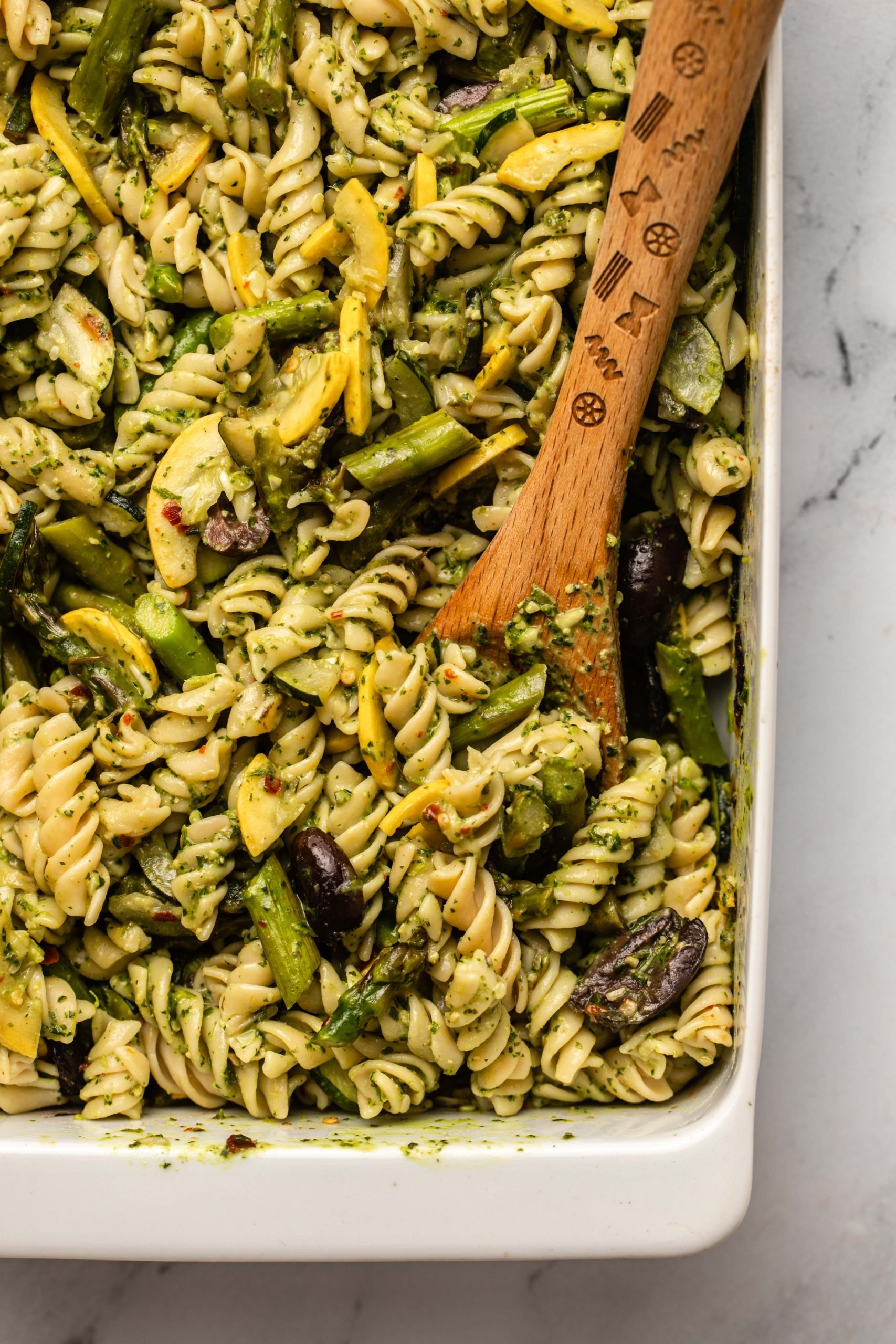 close up photo of roasted vegetable pesto pasta in white casserole dish with pasta mixed in and wooden serving spoon