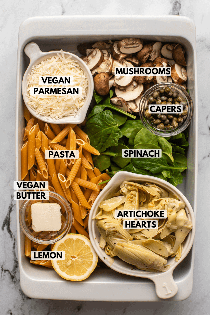 Ingredients for Spinach Artichoke Pasta arranged in white casserole dish. Text labels read vegan parmesan, mushrooms, capers, spinach, pasta, vegan butter, artichoke hearts, and lemon