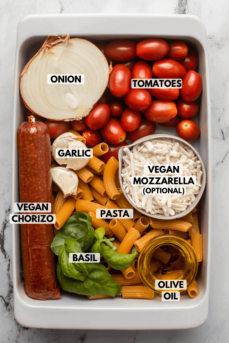 Ingredients for vegan chorizo pasta arranged in white casserole dish. Text labels read onion, tomatoes, garlic, vegan mozzarella, vegan chorizo, pasta, basil, and olive oil