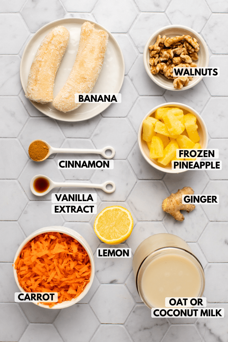 Ingredients for carrot cake smoothie arranged on marble tile background. Text lablels in the photo read banana, walnuts, frozen pineapple, ginger, lemon, oat or coconut milk, carrot, vanilla extract, and cinnamon