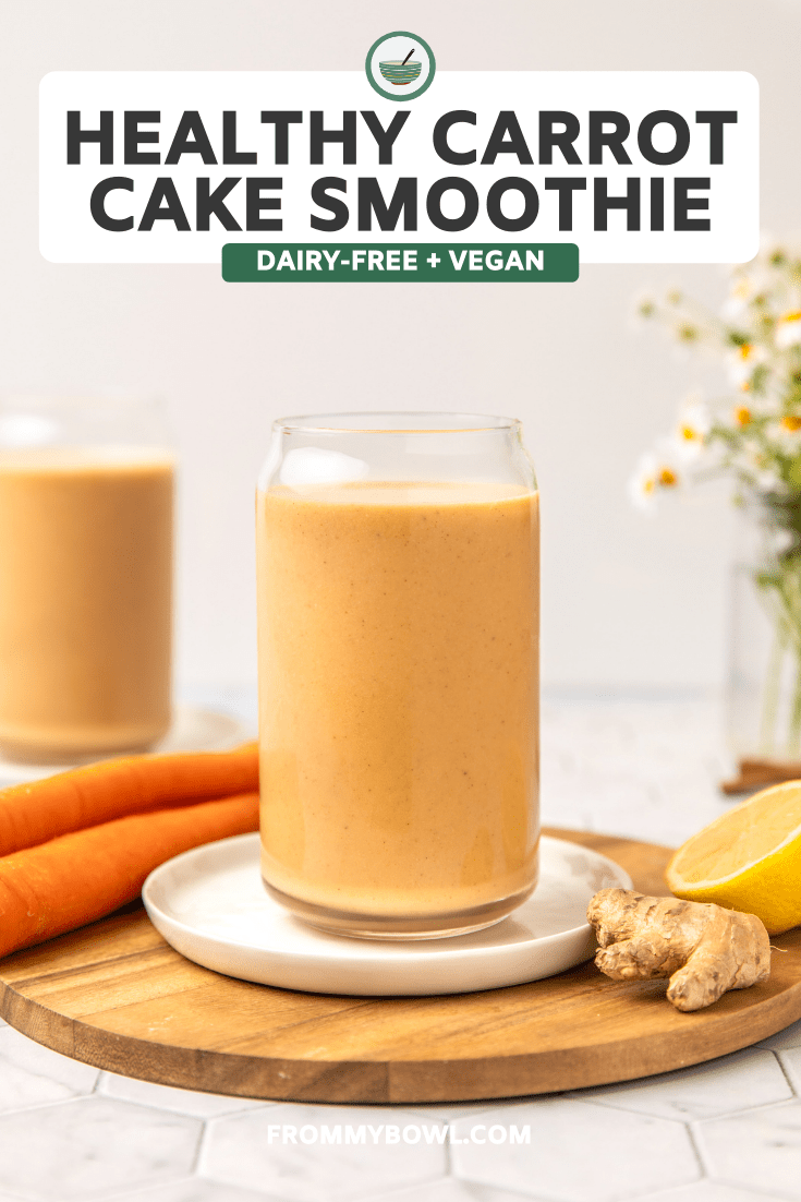 Two glasses of carrot cake smoothie on wooden cutting board with vase of flowers in the background