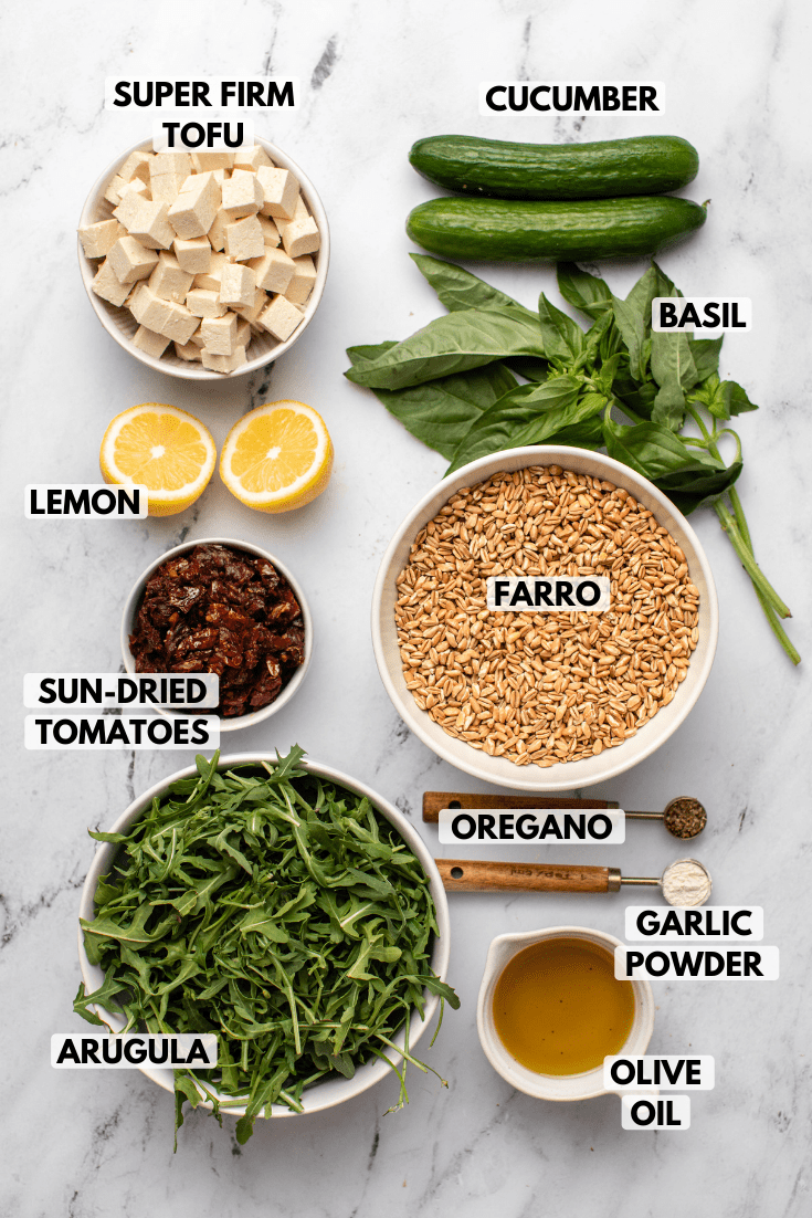 Ingredients for Mediterranean Farro Salad in small white bowls on marble countertop. Clockwise text labels read cucumber, basil, farro, oregano, garlic powder, olive oil, arugula, sun-dried tomatoes, lemon, and super-firm tofu