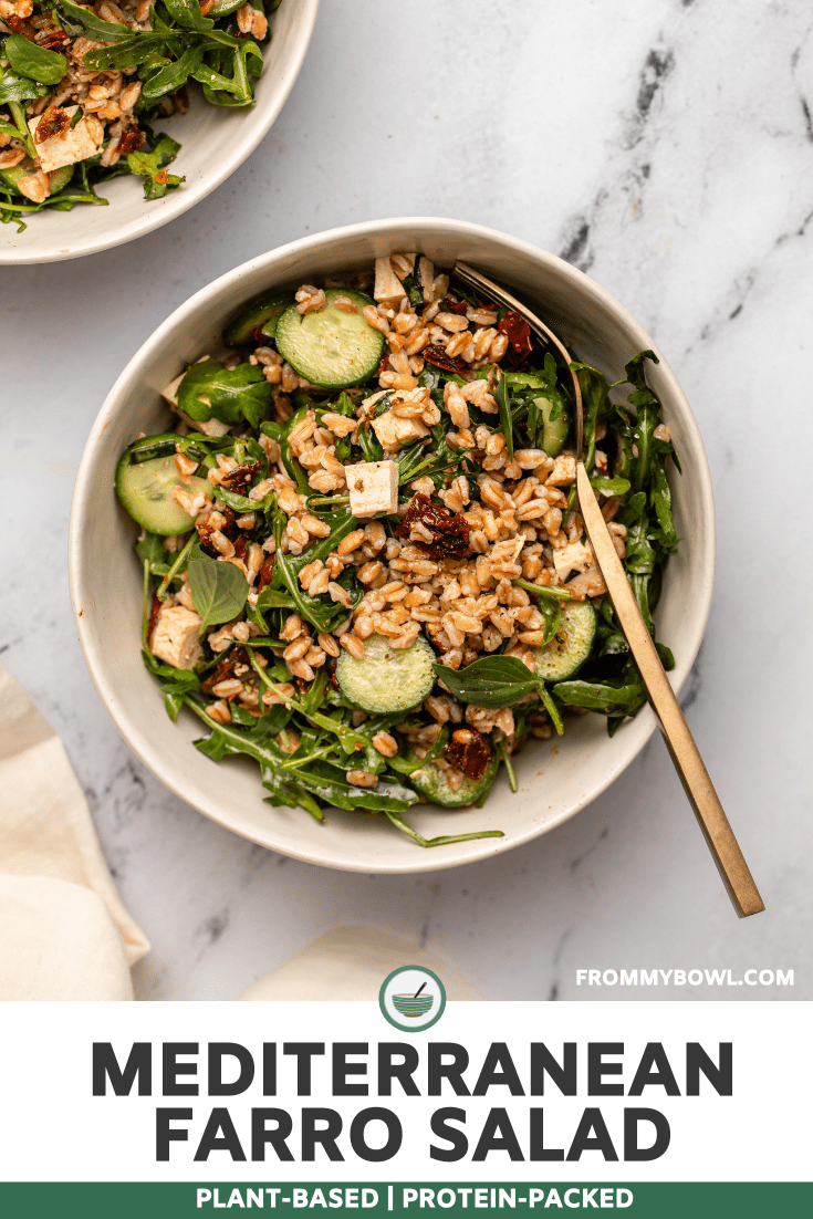 Mediterranean Farro Salad in white bowl with gold fork. A white linen and another bowl of salad are off on the left hand corner