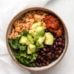 Vegan Burrito Bowl with black beans, salsa, rice, cilantro, and avocado in small speckled bowl on white background
