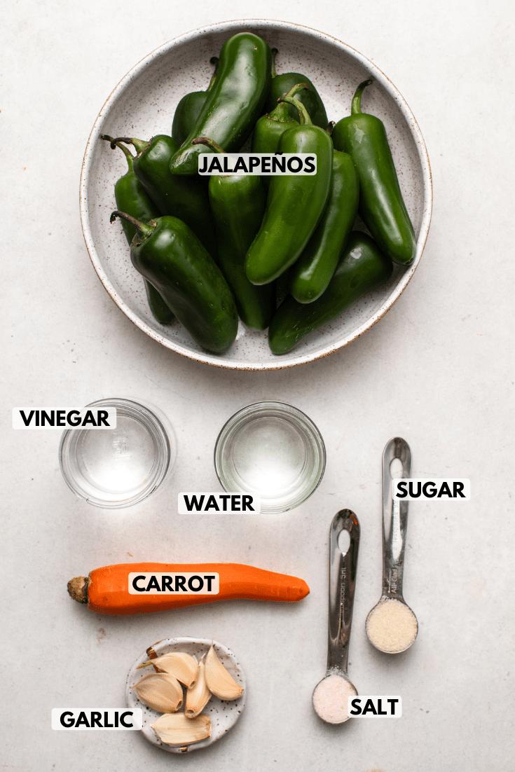 Ingredients for pickled jalapenos arranged on light background. Clockwise text labels read jalapeños, sugar, salt, garlic, carrot, vinegar, and water