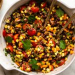 Overhead photo of Tex-Mex black bean salad in large bowl topped with fresh cilantro and gold serving spoons