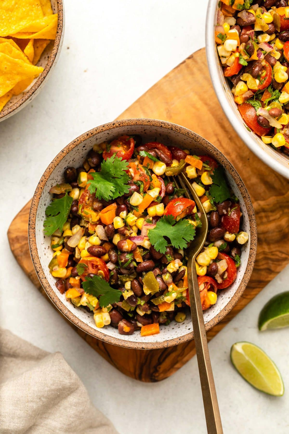 white bowl of tex mex black bean salad topped with fresh cilantro. A gold fork is in the bowl, and the bowl rests on a wood cutting board. Lime wedges and a bowl of tortilla chips are off to the side.