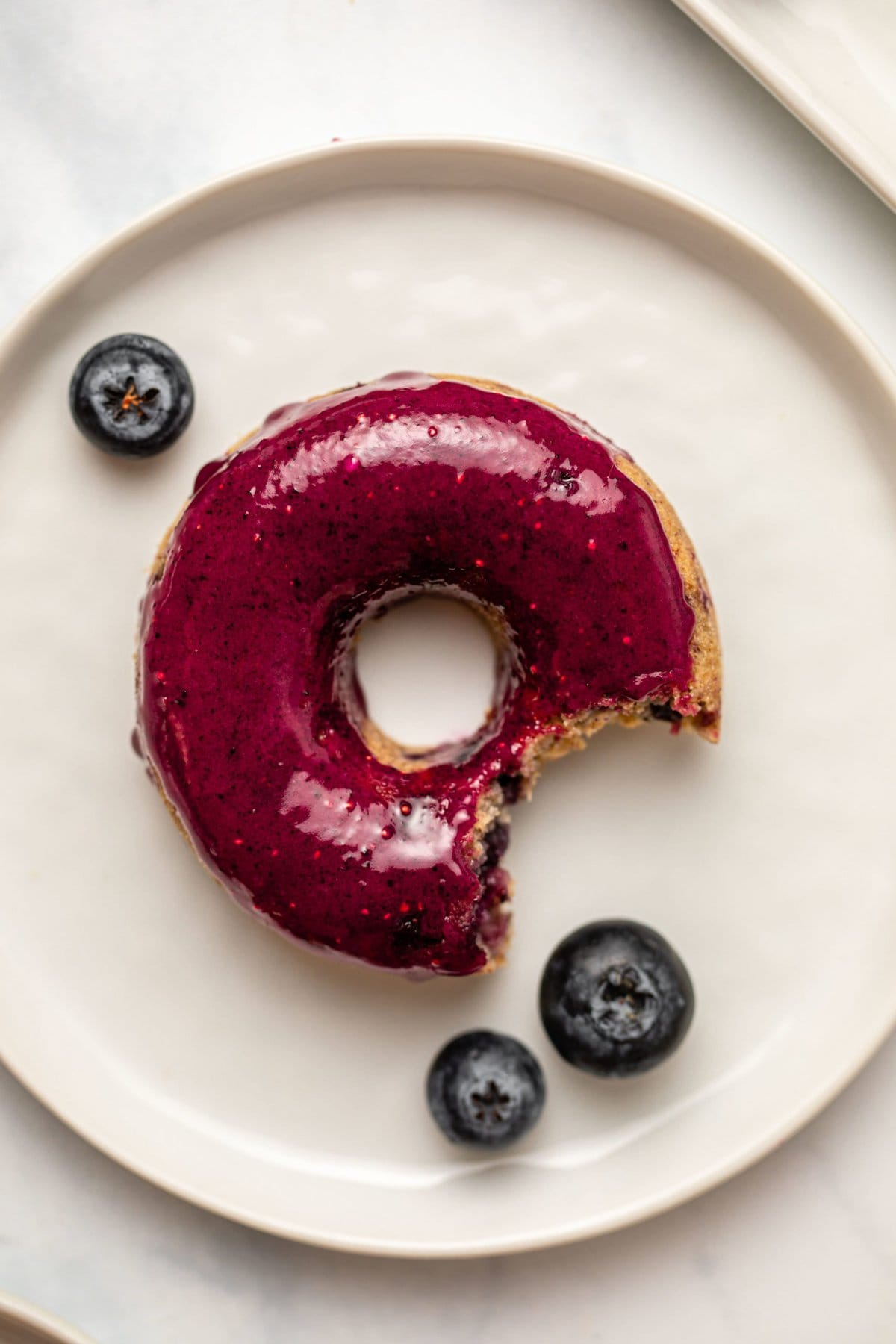 close-up photo of glazed blueberry donut on small white plate with bite taken out of it