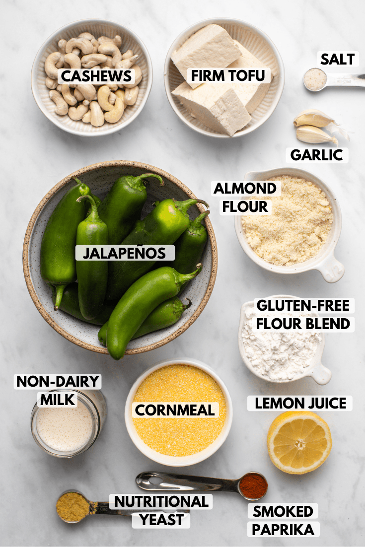 Ingredients for vegan jalapeño poppers arranged in small white bowls on marble background. Clockwise text labels read firm tofu, salt, garlic, almond flour, gluten-free flour blend, lemon juice, smoked paprika, cornmeal, nutritional yeast, non-dairy milk, jalapeños, and cashews