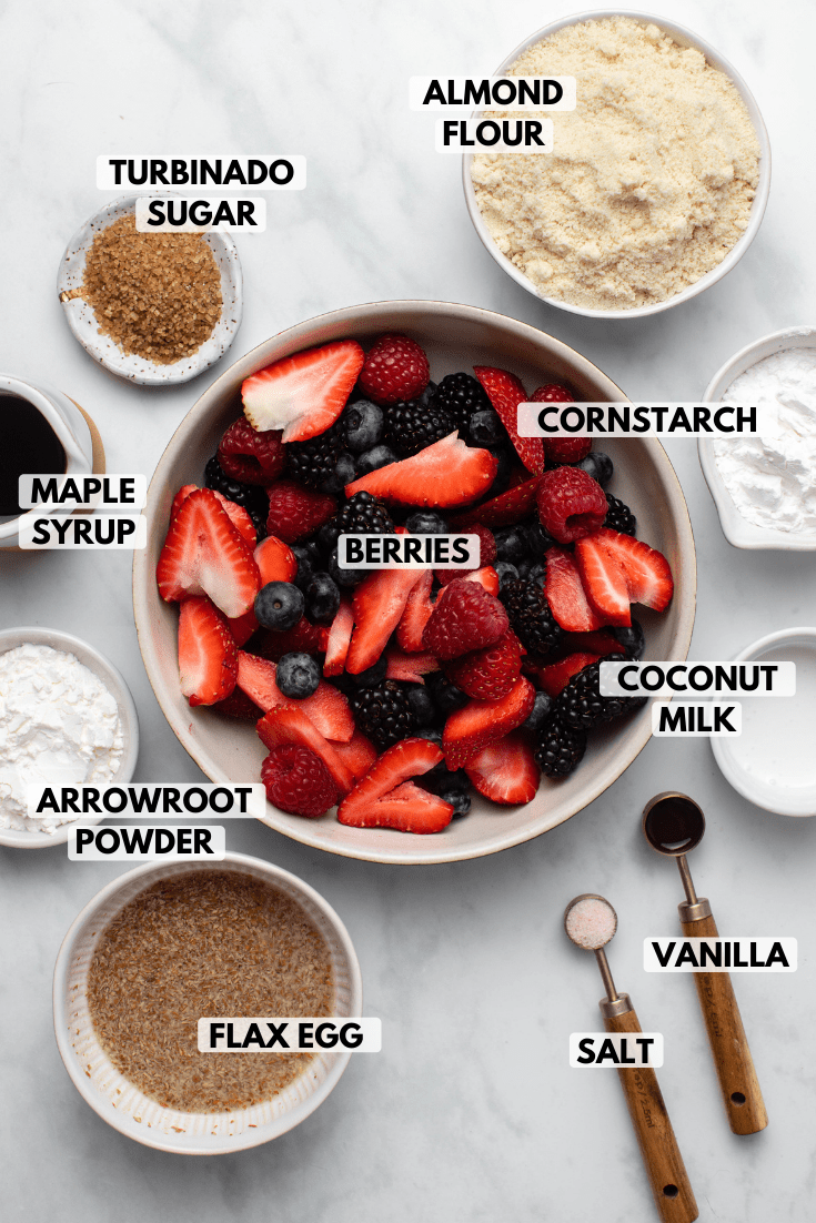 Image of galette ingredients in small white bowls on marble background. Clockwise text labels read almond flour, cornstarch, berries, coconut milk, vanilla, salt, flax egg, arrowroot powder, maple syrup, and turbinado sugar