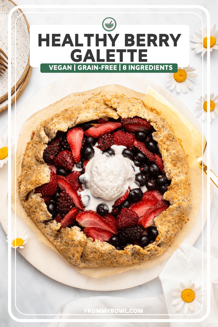 Berry galette topped with melted coco whip on marble serving tray. Fresh flowers lay next to the galette on a white background